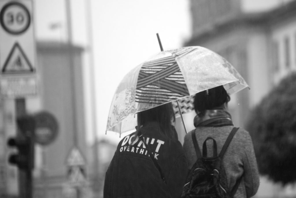 Women with umbrella walking, urban road.